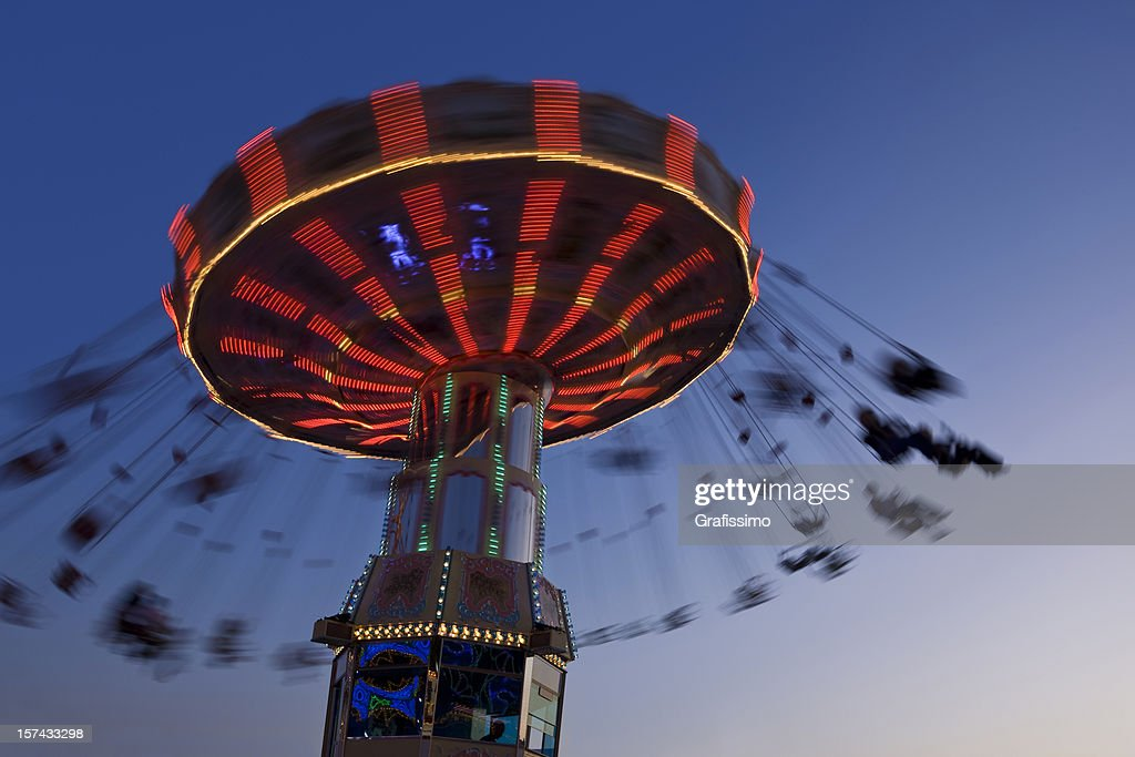 Blurred motion of merry-go-round chairoplane at night : Stock Photo
