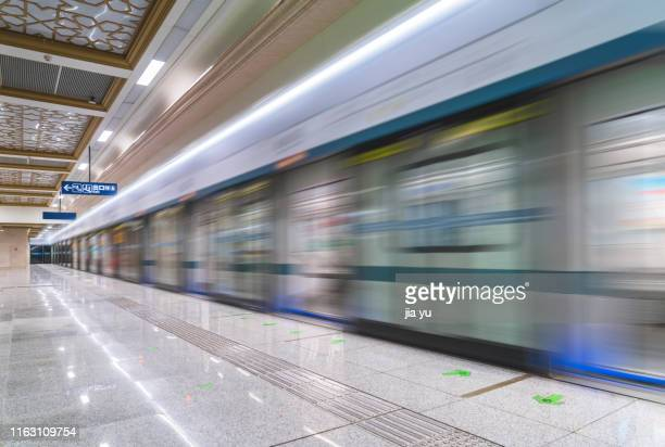 blurred motion of metro at station - underground station stock pictures, royalty-free photos & images