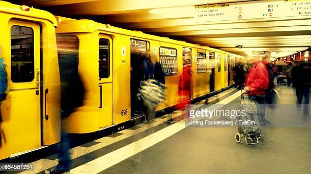 Blurred Motion Of People Boarding In Train At Railroad Station Platform