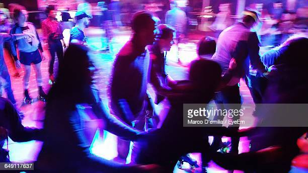 Blurred Motion Of People Enjoying At Roller Disco At Night