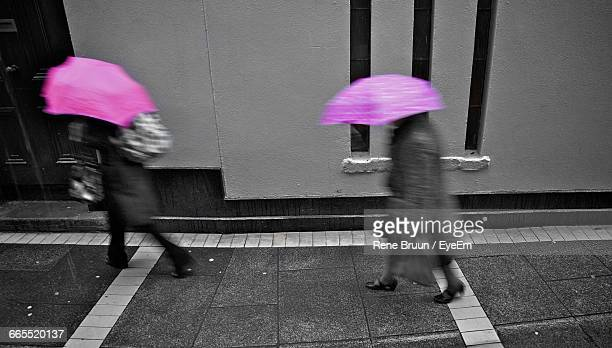 Blurred Motion Of People Holding Umbrellas While Walking On Street