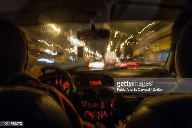 blurred motion of people in car at night - carvajal stock photos and pictures