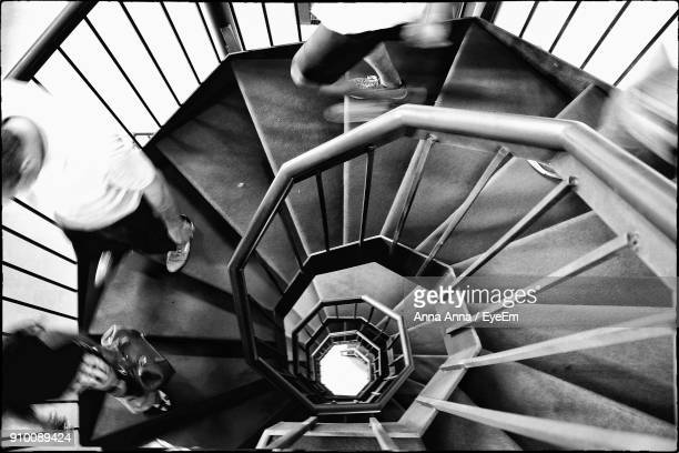 Blurred Motion Of People Moving Down On Spiral Staircase