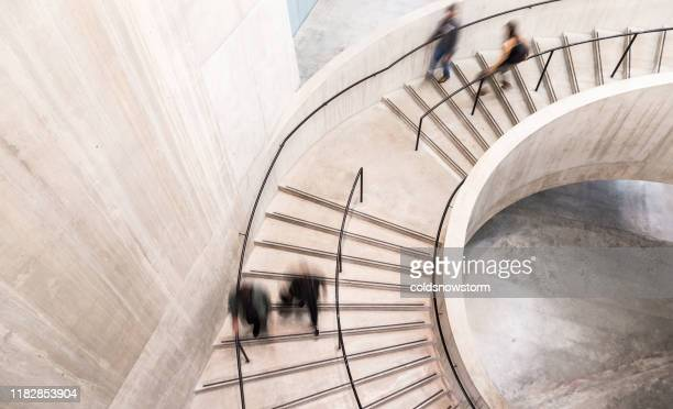 blurred motion of people on spiral staircase - architecture stock pictures, royalty-free photos & images