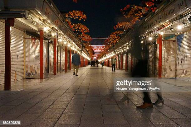 blurred motion of people on walkway amidst stores in city at night - 建具 シャッター ストックフォトと画像