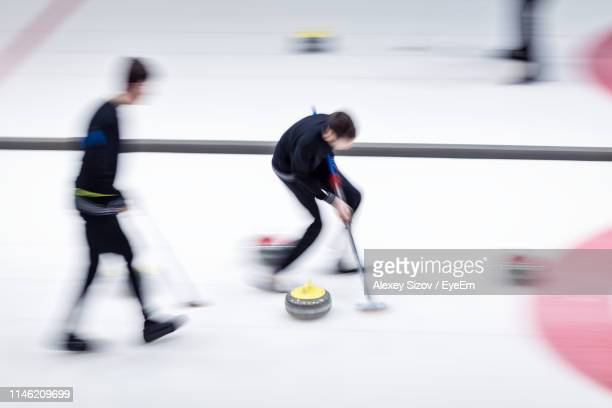 blurred motion of people playing curling - カーリング ストックフォトと画像
