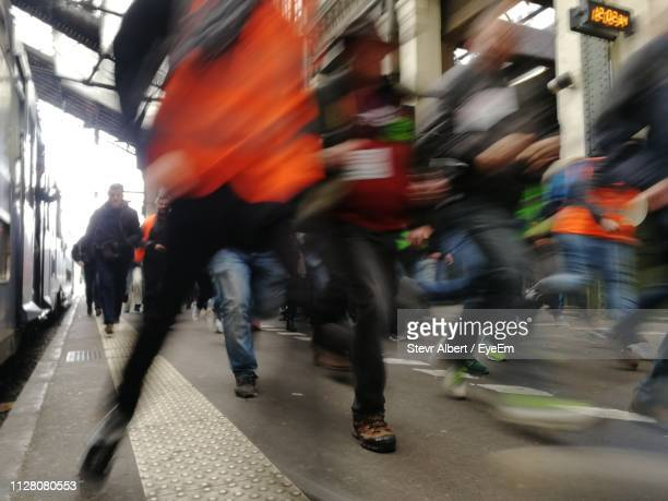 blurred motion of people running at railroad station platform - riot stock pictures, royalty-free photos & images
