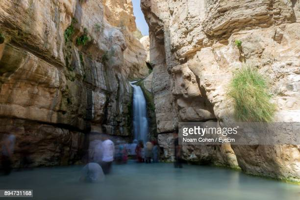 Blurred Motion Of People Standing By Waterfall In River Amidst Rock Formations