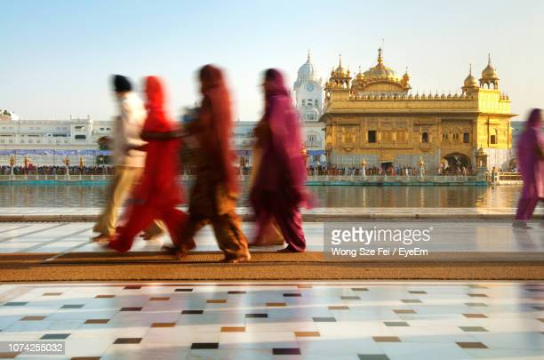 blurred motion of people walking against golden temple - golden temple india stock pictures, royalty-free photos & images