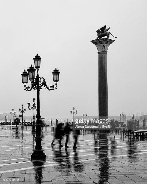 Blurred Motion Of People Walking By Lion Statue On Obelisk At Piazza San Marco Against Sky
