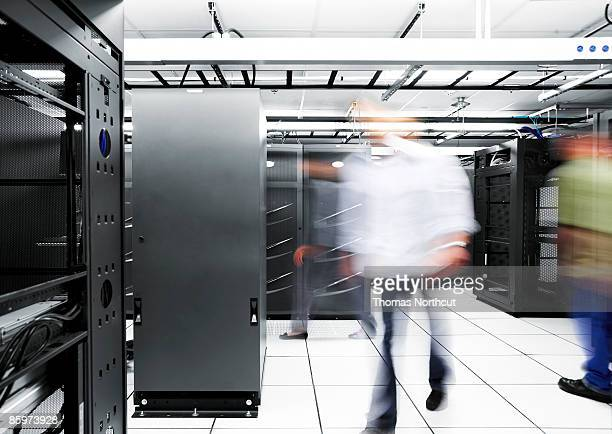 BLurred motion of people walking in a server room.