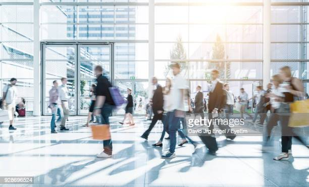 blurred motion of people walking in building - long exposure stock pictures, royalty-free photos & images
