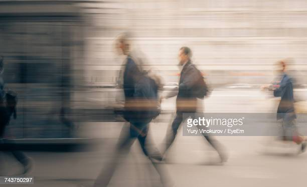 blurred motion of people walking in city - motion blur stock photos and pictures