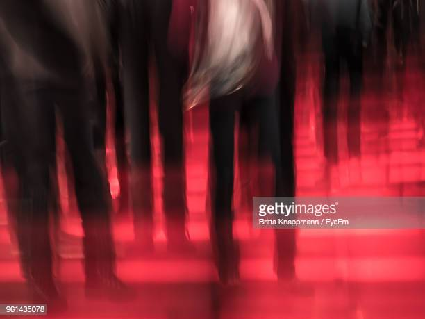 Blurred Motion Of People Walking In Illuminated Nightclub