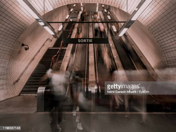blurred motion of people walking in subway station - toulouse photos et images de collection