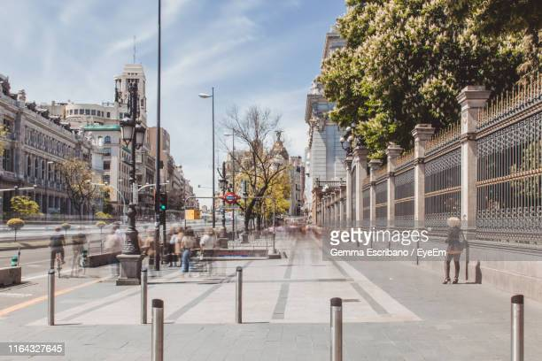 blurred motion of people walking on sidewalk in city during sunny day - street fotografías e imágenes de stock