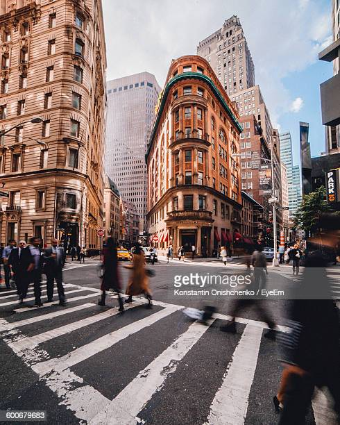 blurred motion of people walking on street against buildings in city - lower manhattan stock photos and pictures
