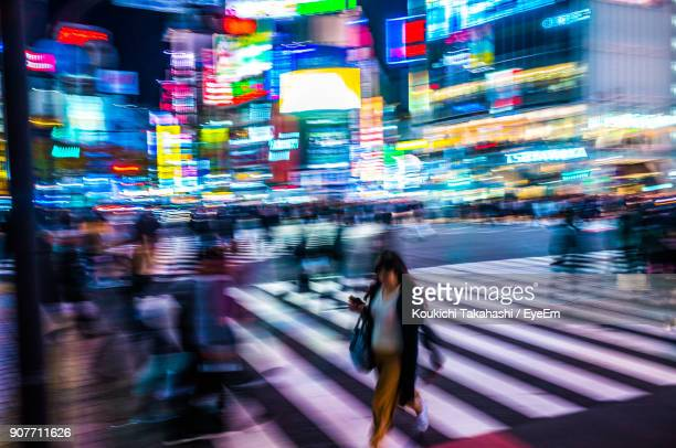 Blurred Motion Of People Walking On Street At Night