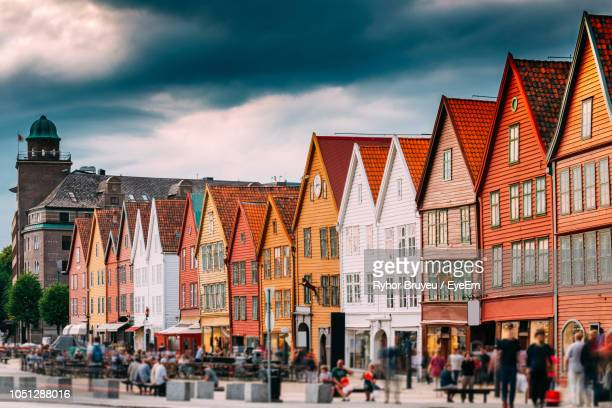 blurred motion of people walking on street by houses in town - bergen norway stock pictures, royalty-free photos & images