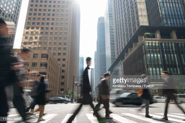 blurred motion of people walking on street in city - 丸の内 ストックフォトと画像