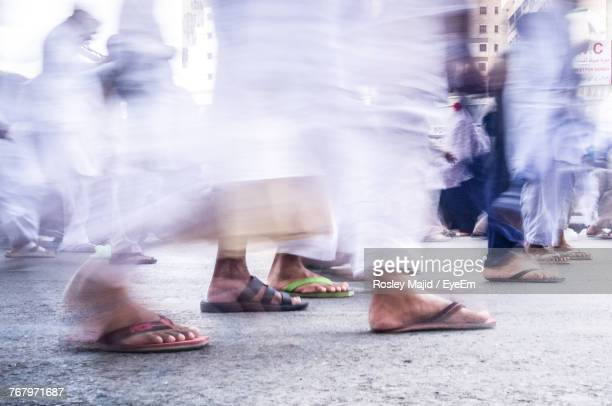 blurred motion of people walking on street - arab feet photos et images de collection