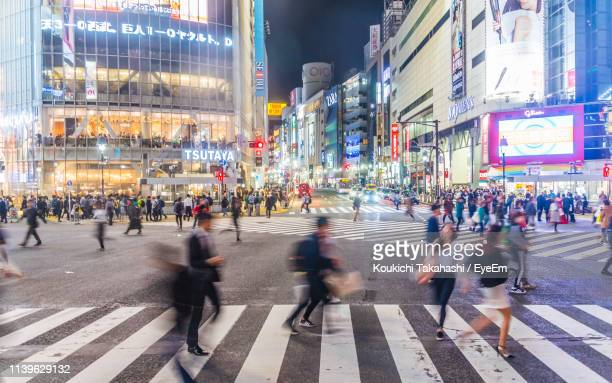 Blurred Motion Of People Walking On Zebra Crossing In City At Night