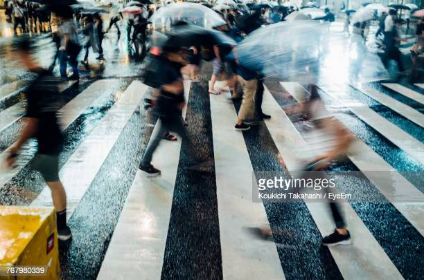 Blurred Motion Of People Walking With Umbrella On Road
