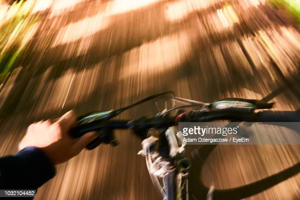 blurred motion of person cycling on road - handlebar stock photos and pictures
