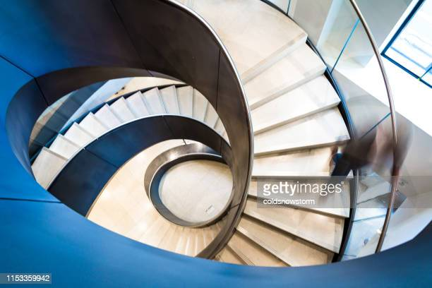 blurred motion of person on abstract spiral staircase - curve stock pictures, royalty-free photos & images