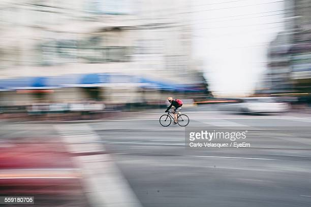 Blurred Motion Of Person Riding Bicycle On City Road
