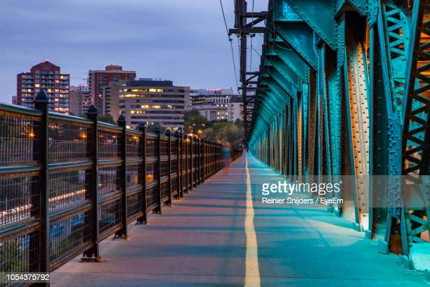 blurred motion of person walking on bridge during sunset - edmonton stock pictures, royalty-free photos & images