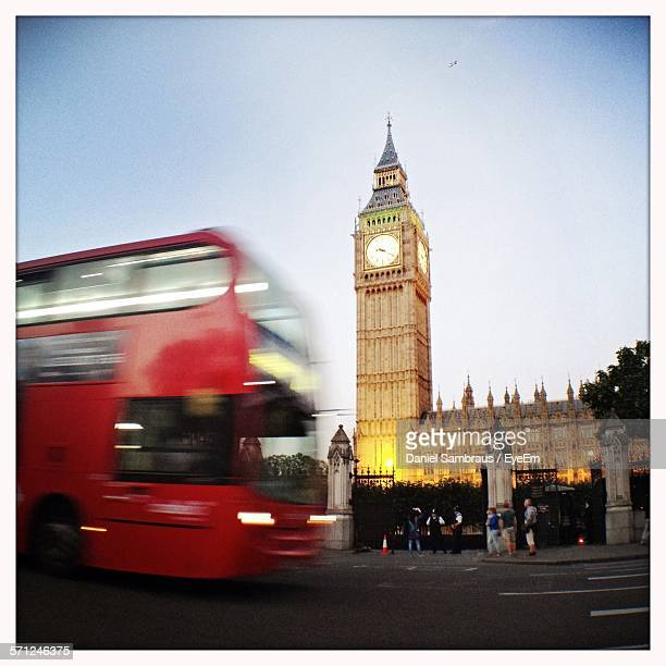 Blurred Motion Of Red Bus On Street With Big Ben Seen In Background