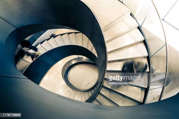 wazig beweging van snelheid zakenman op abstracte wenteltrap - onherkenbaar persoon stockfoto's en -beelden