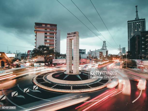 blurred motion of traffic in city during sunset - metro manila stock photos and pictures