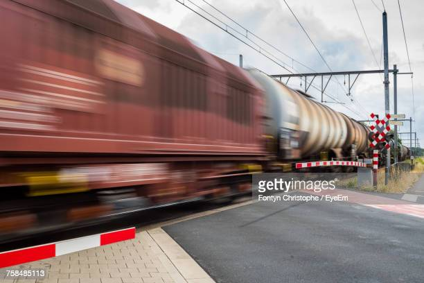 blurred motion of train against sky - railroad crossing stock pictures, royalty-free photos & images