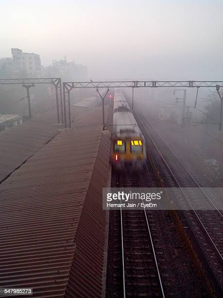 Blurred Motion Of Train Arriving At Railroad Station Platform During Foggy Weather