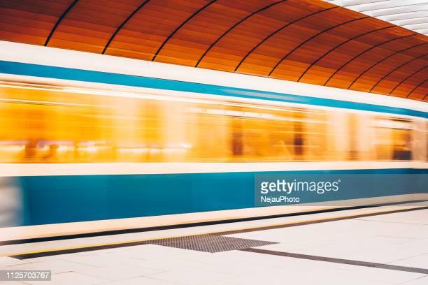 blurred motion of train at railroad station - ubahn stock-fotos und bilder