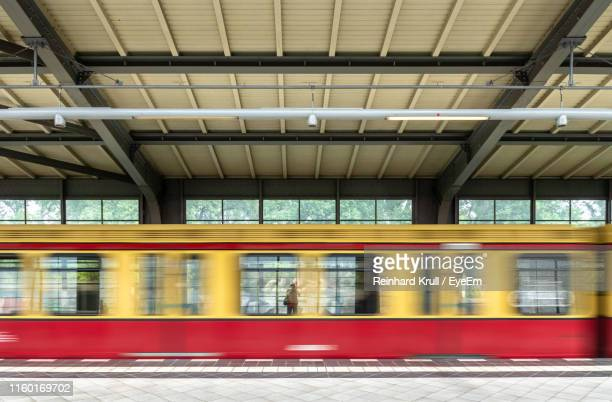 blurred motion of train at railroad station platform - railroad station platform stock pictures, royalty-free photos & images