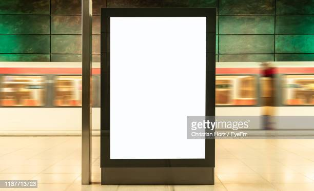 blurred motion of train at subway station with blank billboard in foreground - subway station stock pictures, royalty-free photos & images