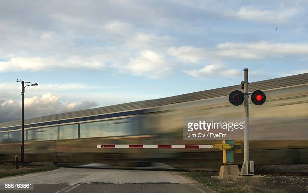 blurred motion of train by railroad crossing against sky - railroad crossing stock pictures, royalty-free photos & images