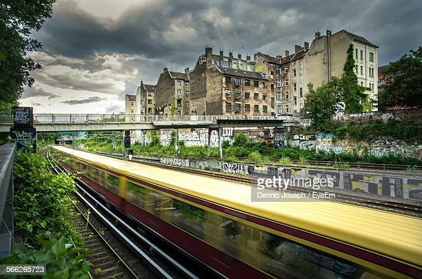 Blurred Motion Of Train In Front Of Buildings In City Against Cloudy Sky