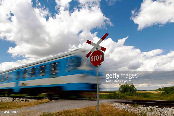 Blurred Motion Of Train Passing By Railroad Crossing Against Sky