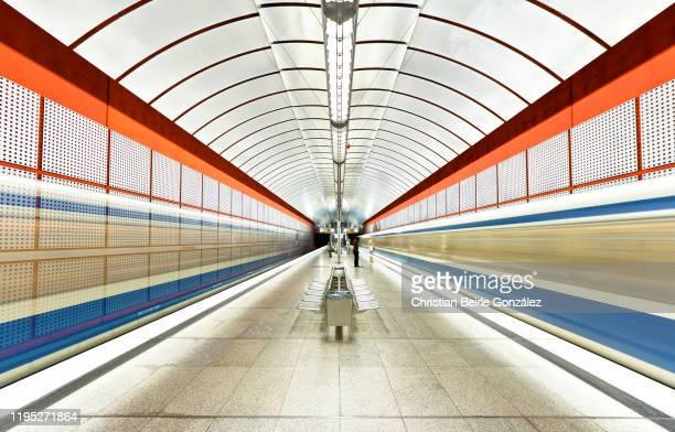 blurred motion of trains at subway station kreillerstrasse, munich, germany - christian beirle stockfoto's en -beelden