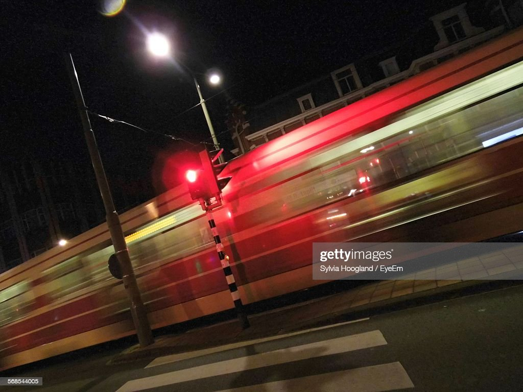 Blurred Motion Of Tram By Illuminated Road Signal On Street At Night : Stock Photo