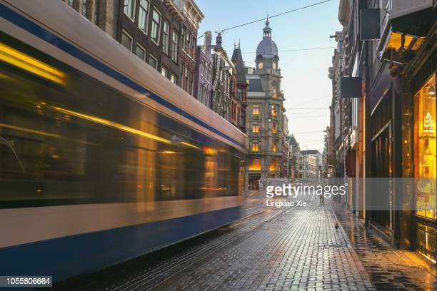blurred motion of tram running on leidsestraat street at dawn, amsterdam, netherlands - europäische kultur stock-fotos und bilder