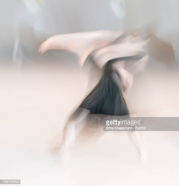 Blurred Motion Of Woman Dancing Against White Background