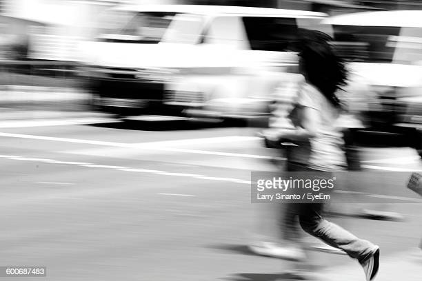Blurred Motion Of Woman Running On Road In City