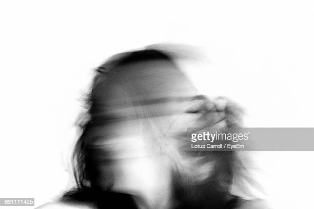 Blurred Motion Of Woman Shaking Head Against White Background