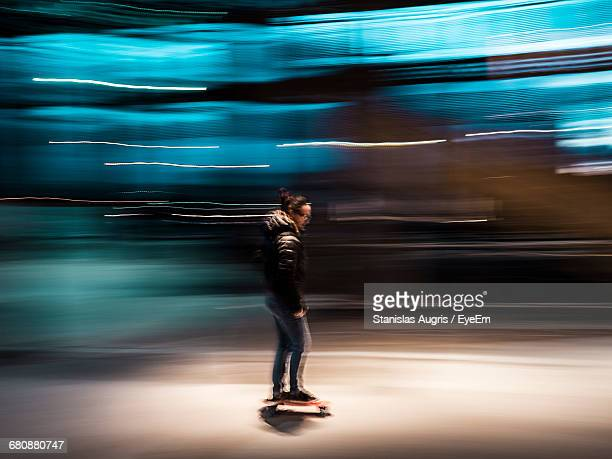 Blurred Motion Of Woman Skateboarding On Street At Night