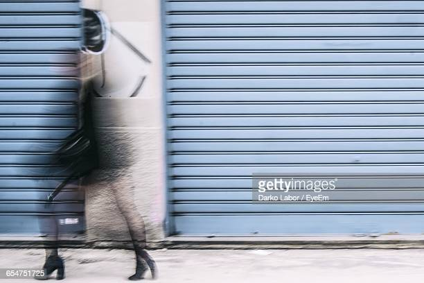 blurred motion of woman walking on street - fast shutter speed stock photos and pictures